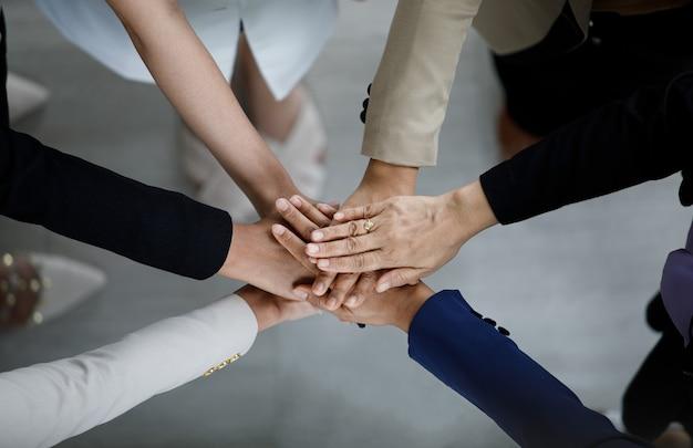 Widok z góry bliska strzał profesjonalnej grupy biznesmenów businesswoman współpracowników partnerstwa zespołu ręce trzymając razem dla firmy silne zaufanie do pracy zespołowej jedność osiągnięcia zobowiązania.