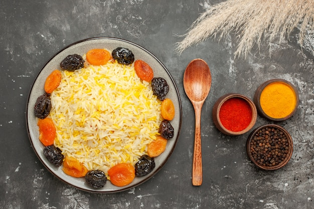 Widok z góry bliska talerz ryżowy z ryżem z suszonymi owocami łyżka kolorowe przyprawy