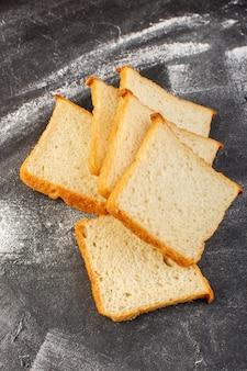 Widok z góry bochenki chleba białego pokrojone w plasterki i smaczne samodzielnie na szarym tle drożdżówka chleb żywności