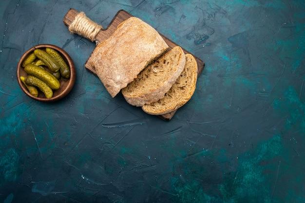 Widok z góry bochenki chleba z piklami na granatowym biurku.