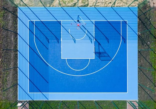 Widok z góry boisko do koszykówki. niebieskie boisko sportowe z długimi cieniami w świetle dziennym z lotu ptaka.