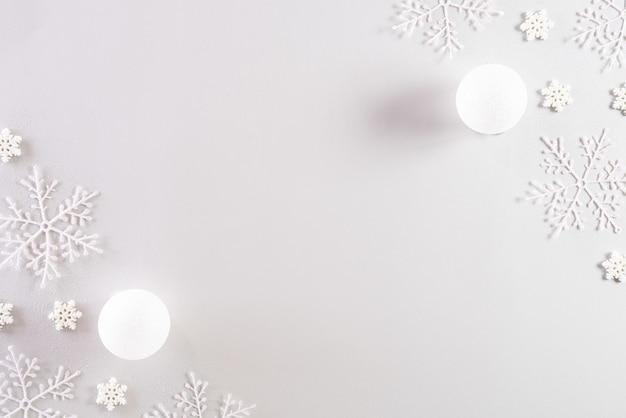 Widok z góry bombki z płatki śniegu na jasnoszarym pastelowym tle.