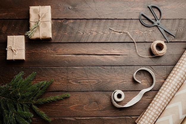 Widok z góry boże narodzenie tło z drewnianym stołem i rustykalnym opakowaniem na prezent dostarcza miejsca na kopię