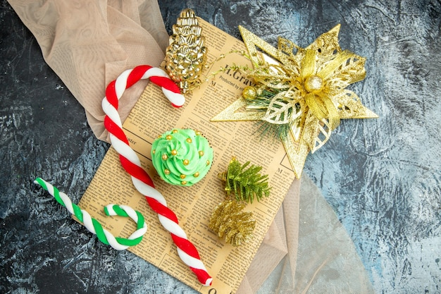 Widok z góry bożonarodzeniowe ciastko świąteczne cukierki świąteczne ozdoby na gazetowym beżowym szalu na ciemnej powierzchni