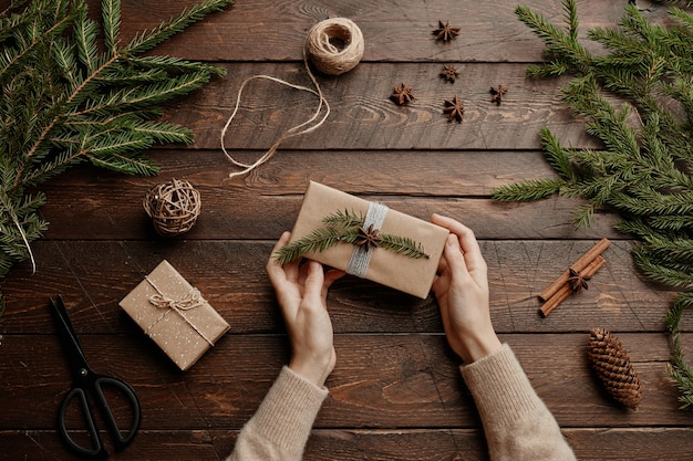 Widok z góry bożonarodzeniowe tło z nierozpoznawalną młodą kobietą pakującą prezenty na drewnianym stole...