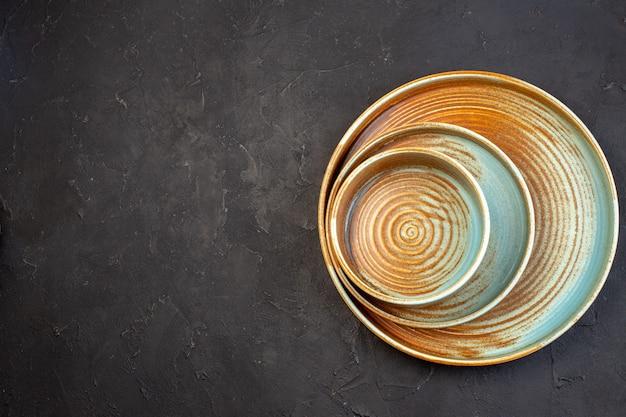 Widok z góry brązowa duża taca z tym samym kolorowym talerzem na ciemnej powierzchni