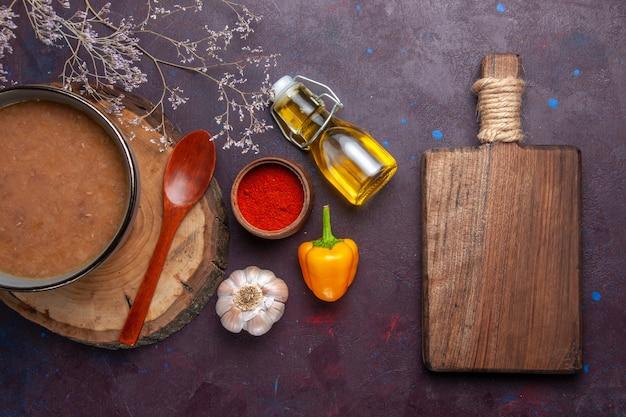 Widok z góry brązowa zupa z oliwą z oliwek i czosnkiem na ciemnej podłodze zupa posiłek warzywny jedzenie fasola