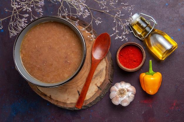 Widok z góry brązowa zupa z oliwą z oliwek i czosnkiem na ciemnej powierzchni zupa posiłek warzywny jedzenie fasola