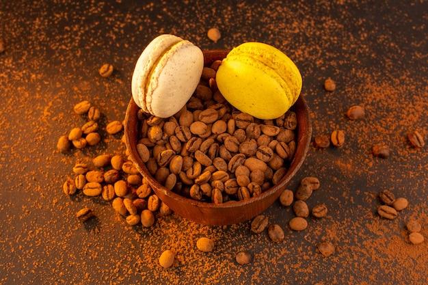 Widok z góry brązowe ziarna kawy wewnątrz brązowego talerza z makaronikami na brązowym stole