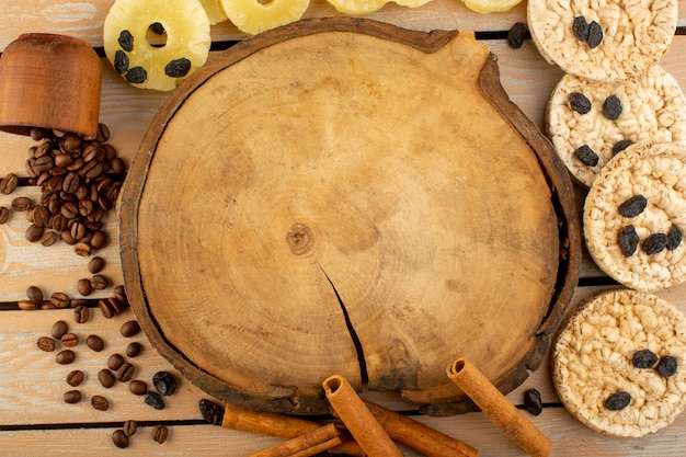 Widok z góry brązowe ziarna kawy z krakersami cynamonem i suszonym ananasem na kremowym stole rustykalnym biszkoptowym ziarnku kawy