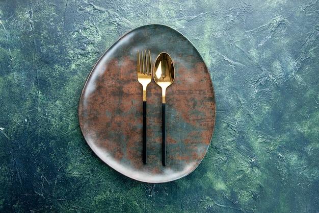 Widok z góry brązowy pusty talerz ze złotą łyżką na ciemnym tle restauracja jedzenie kuchnia posiłek utencil sztućce obiad
