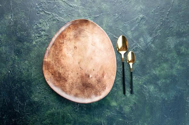 Widok z góry brązowy talerz ze złotymi łyżkami na ciemnoniebieskim tle obiad sztućce posiłek jedzenie restauracja naczynie kolor tabeli
