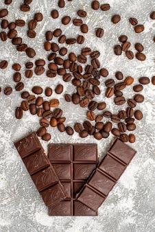 Widok z góry brązowych nasion kawy z batonami czekolady na białej powierzchni