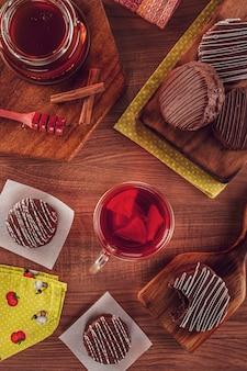 Widok z góry brazylijskiej czekolady miodowej pokrytej na drewnianym stole przezroczystym kubkiem herbaty, pszczoły miodnej i cynamonem - pă £ o de mel
