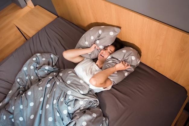 Widok z góry brunetki kobiety z nieszczęśliwym wyrazem twarzy zamykającej uszy poduszkami podczas leżenia w łóżku