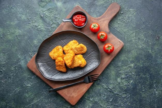 Widok z góry bryłek kurczaka na czarnej płycie i widelec na drewnianej desce keczup pomidory na ciemnej powierzchni