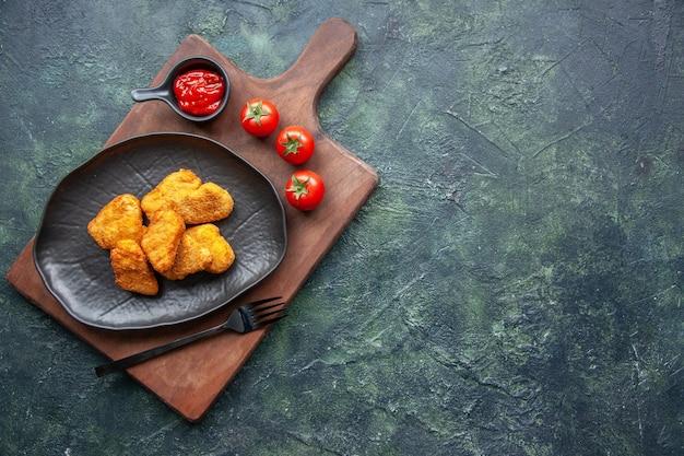 Widok z góry bryłek kurczaka na czarnej płycie i widelec na drewnianej desce pomidory keczup po prawej stronie na ciemnej powierzchni