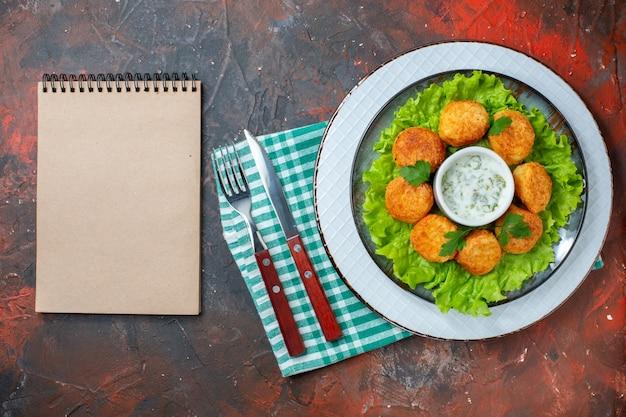 Widok z góry bryłki kurczaka z sałatą na talerzu czarny pieprz w misce widelec i nóż notatnik na ciemnym stole