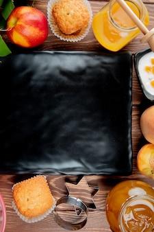 Widok z góry brzoskwiniowy brzoskwiniowy dżem babeczki twarogu z talerzem na centrum na drewnianej powierzchni