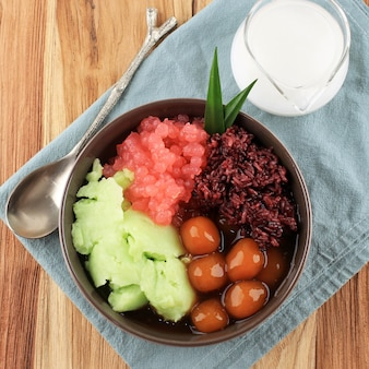 Widok z góry bubur madura, jawajska owsianka deserowa z owsianki z mąki ryżowej (bubur sumsum), kulki ze słodkich ziemniaków (candil), perła tapioki i czarny lepki ryż.