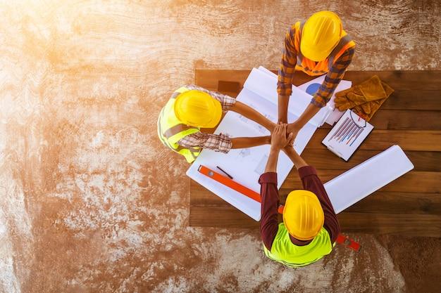 [widok z góry budowa pracy zespołowej] zespół inżynierów i architektów łączy ręce, aby budować udane projekty. koncepcja pracy zespołowej.