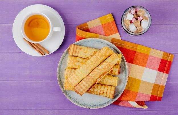 Widok z góry bułki waflowej wypełnionej skondensowanym mlekiem na talerzu i kostkami cukru w szklanym słoju z zieloną herbatą na drewnianej fioletowej powierzchni