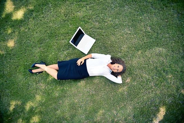 Widok z góry businesswoman leżącego na trawie
