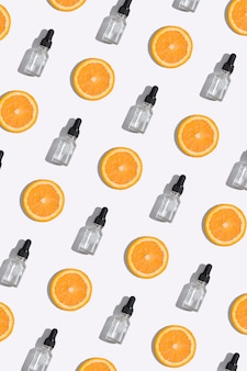 Widok z góry butelka kroplomierzem witaminy c serum, olej kosmetyczny i plastry pomarańczy na białym tle. kreatywne tło wzór kosmetyków w formacie pionowym do opowiadań