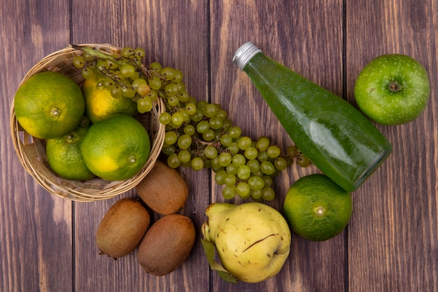 Widok z góry butelka soku z gruszka kiwi mandarynki jabłka i winogrona w koszu na drewnianej ścianie