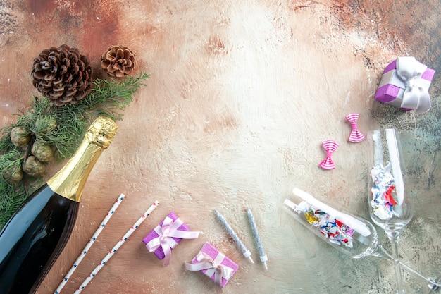 Widok z góry butelka szampana z małymi prezentami na lekkim świątecznym zdjęciu prezent w kolorze alkoholu na nowy rok