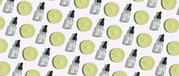 Widok z góry butelka z zakraplaczem witaminy c serum, olej kosmetyczny i plasterki limonki na białym tle. kreatywny wzór kosmetyków w formacie banera