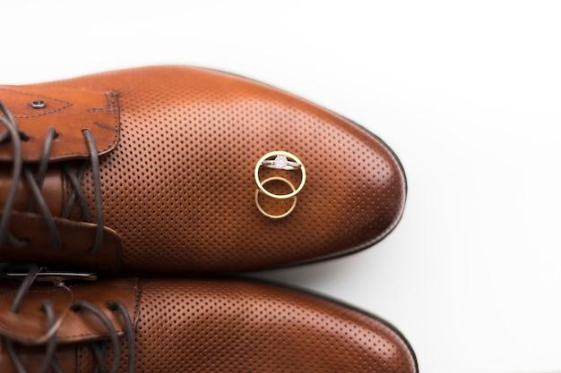 Widok z góry buty pana młodego z pierścionkami zaręczynowymi