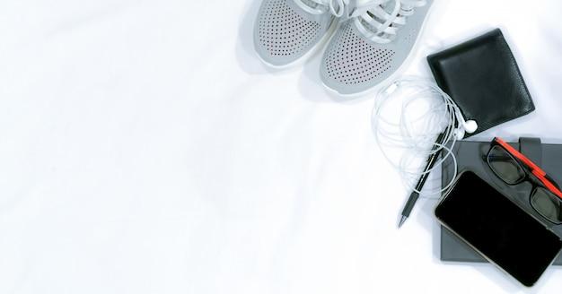 Widok z góry buty, smartfon, portfel, słuchawki, okulary, notatnik i ołówek na białym biurku z miejsca kopiowania. widok z góry moda w stylu casual na wakacje.