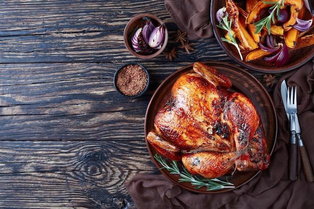 Widok z góry całego pieczonego kurczaka ze złotobrązową chrupiącą skórką podanego na glinianym naczyniu z karmelizowanymi grillowanymi plastrami dyni i grillowaną cebulą, widok z góry, układanie na płasko, miejsce na kopię