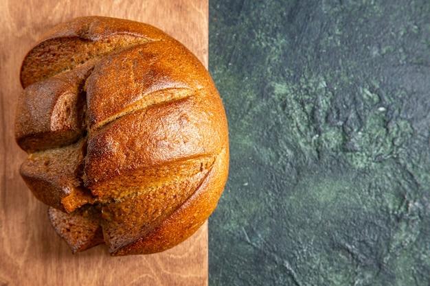 Widok z góry całego świeżego czarnego chleba na brązowej drewnianej desce do krojenia po prawej stronie na powierzchni ciemnych kolorów