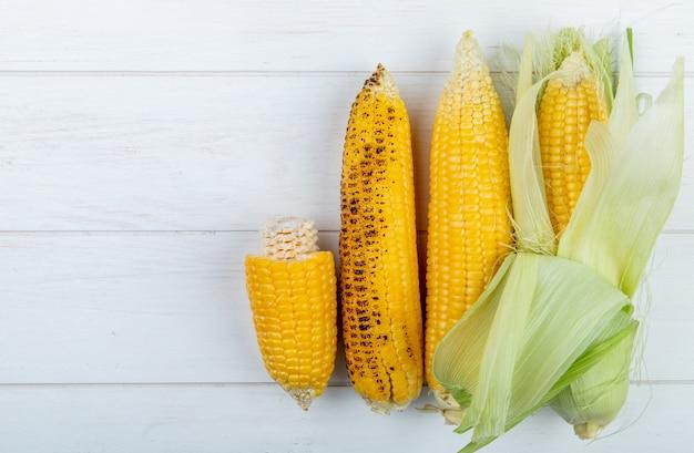 Widok z góry całych i ciętych kolb kukurydzy na drewnianej powierzchni z miejsca kopiowania