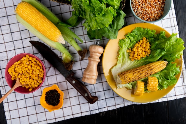Widok z góry całych i pokrojonych ziaren i nasion kukurydzy z sałatą w talerzu i nożem szpinakowym czarny pieprz na kraciastym materiale i czarnej powierzchni