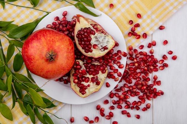 Widok z góry całych kawałków granatu i kawałków granatu z jagodami na talerzu i liśćmi na kraciastej tkaninie z jagodami granatu na drewnianej powierzchni