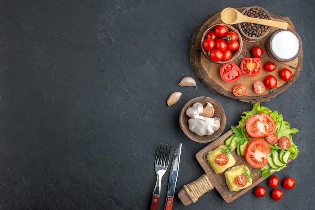 Widok z góry całych pokrojonych świeżych warzyw i przypraw na drewnianej desce zestaw sztućców ręcznik biały ser na czarnej powierzchni