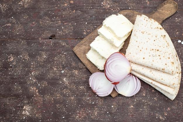 Widok z góry cebula białego sera w plasterkach na szarym biurku ze zdjęciem mączki warzywnej żywności lawaszowej