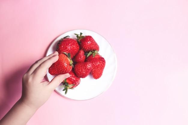 Widok z góry childs ręka trzyma truskawkę na różowym stole, talerz truskawek. koncepcja zdrowego odżywiania w lecie.