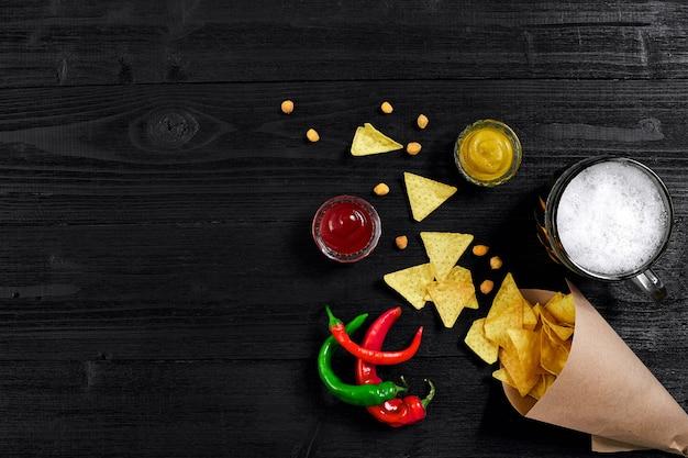 Widok z góry chipsów tortilla ze szklanką sosu piwa i czerwonej papryczki chili na czarnym drewnianym tle