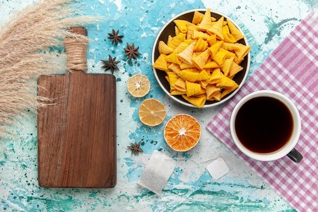 Widok z góry chipsy do krakowania z filiżanką herbaty na niebieskiej powierzchni