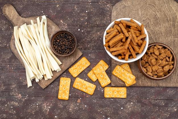 Widok z góry chipsy i krakersy z serem na brązowym drewnianym biurku przekąska ze zdjęciem chrupiącego krakersa
