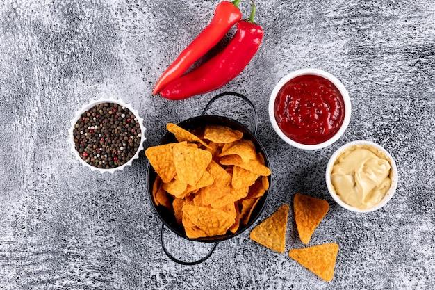 Widok z góry chipsy w czarnej metalowej patelni i przyprawy z sosami w miskach na białym kamieniu