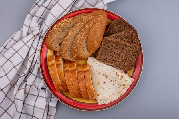 Widok z góry chleba jako pokrojona w plasterki bagietka żytnia z brązowej kolby i podpłomyki na talerzu na kraciastej szmatce na szarym tle