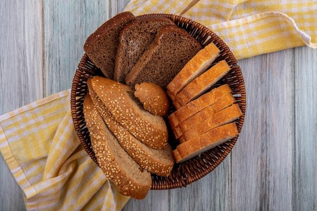 Widok z góry chleba jako pokrojony w plasterki brązowy żytni kaczan i chrupiący w koszu na kraciastej tkaninie na drewnianym tle