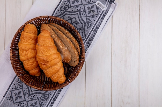 Widok z góry chleba jako rogalika i posianych kromek chleba z brązowej kolby w koszu na tkaninie na drewnianym tle z miejsca na kopię
