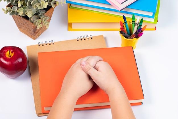 Widok z góry chłopiec dołączyć rękę razem na stos książek na białym tle / powrót do szkoły