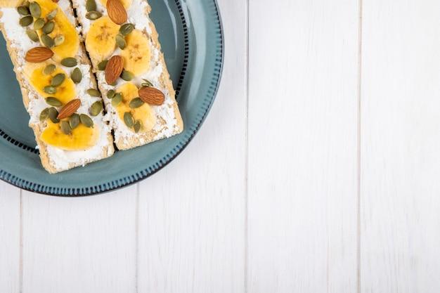 Widok z góry chrupiących krakersów z twarogiem, plasterkami banana, migdałów i pestek dyni na talerzu na białym drewnie z miejsca kopiowania